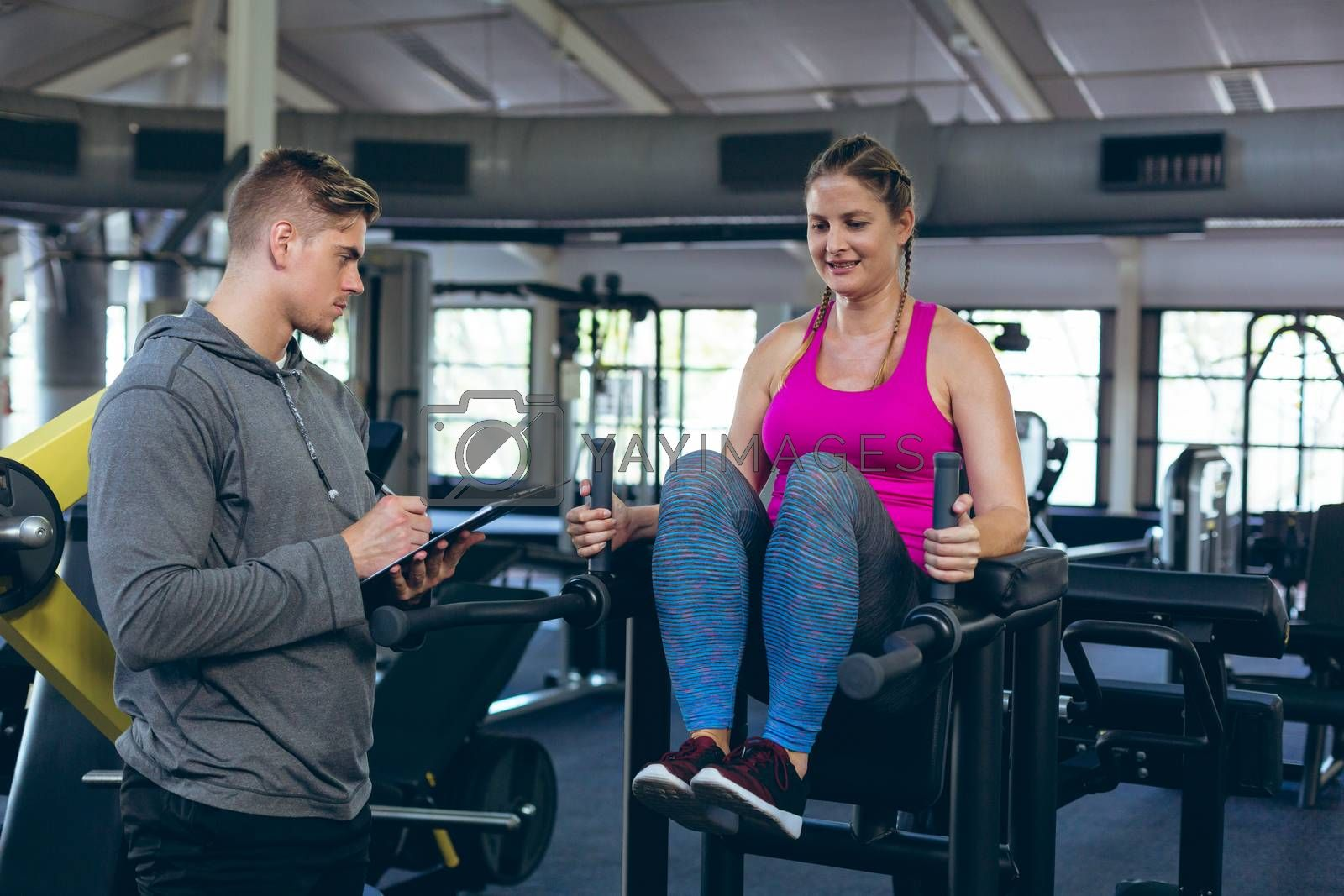 Side view of Caucasian Male trainer assisting young Caucasian female athlete with exercise in fitness studio. Bright modern gym with fit healthy people working out and training