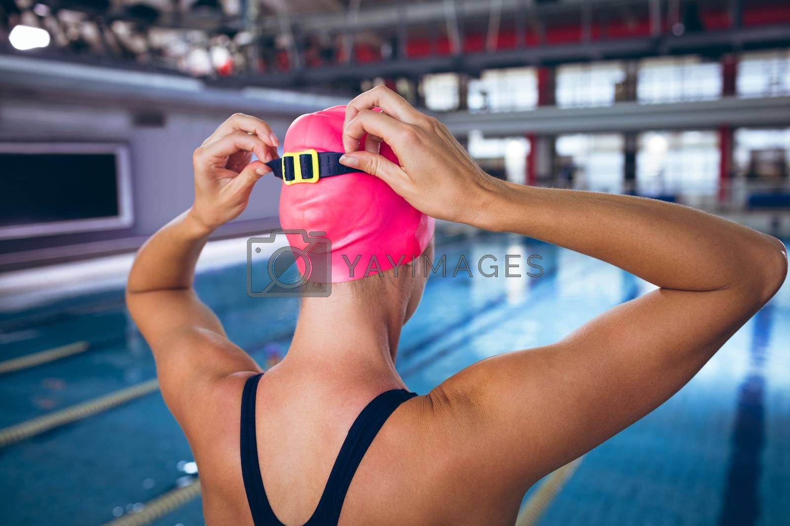 Rear view of a Caucasian woman wearing a swimsuit and a pink swimming cap with goggles standing by an olympic sized pool inside a stadium. Bright modern gym with fit healthy people working out and training