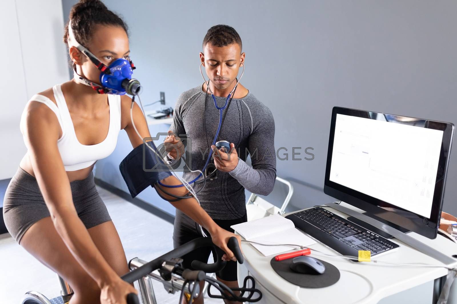 Side view of an African-American athletic woman doing a fitness test using a mask connected to a monitor while riding an exercise bike and an African-American man measuring her blood pressure inside a room at a sports center. Bright modern gym with fit healthy people working out and training. Athlete testing themselves with cardiovascular fitness test on exercise bike