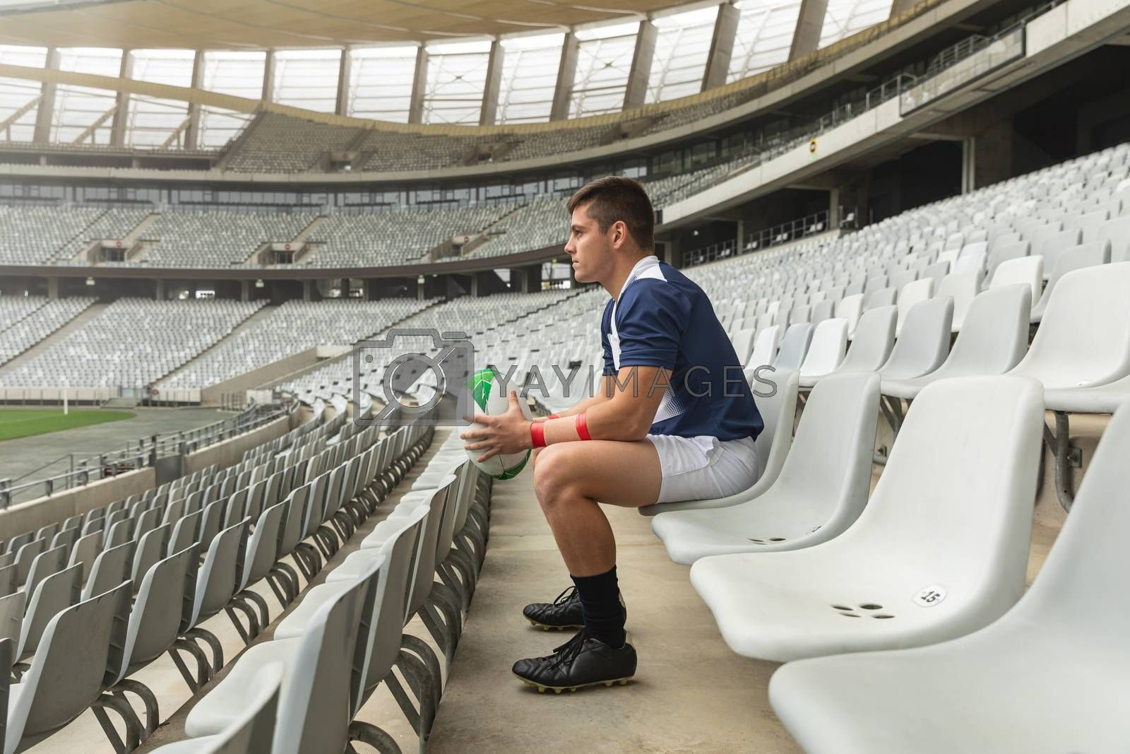 Side view of thoughtful Caucasian male rugby player sitting with rugby ball in stadium