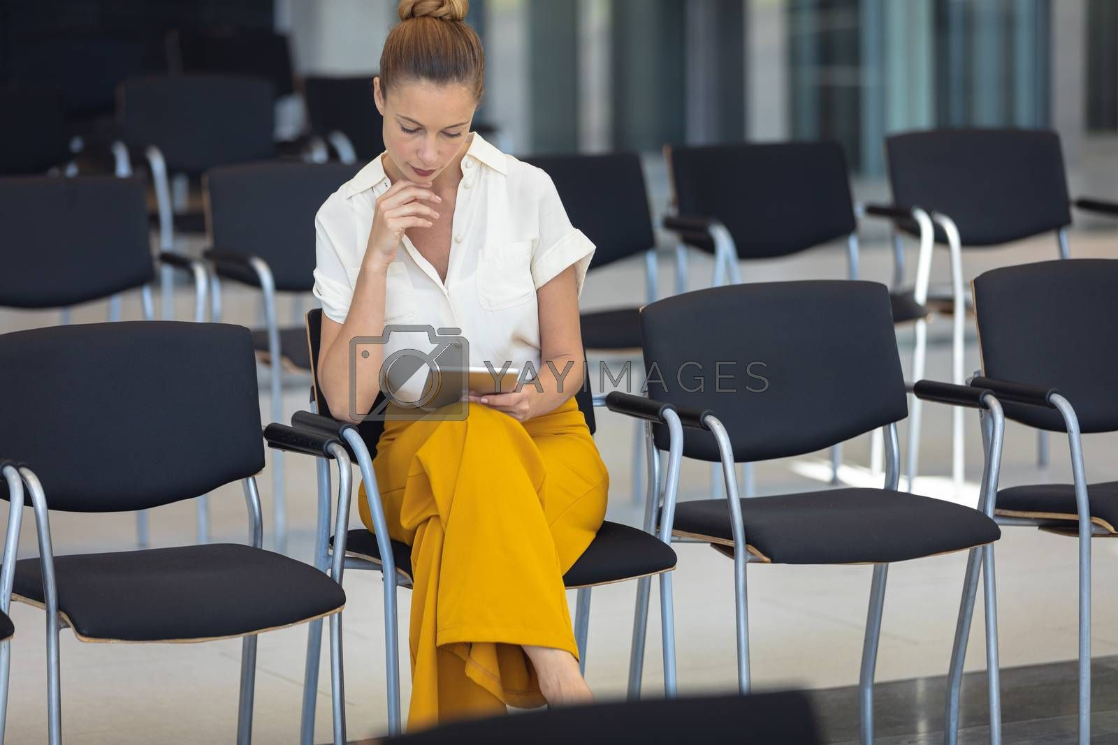 Front view of young Caucasian female executive looking at digital tablet while sitting on chair in empty conference room