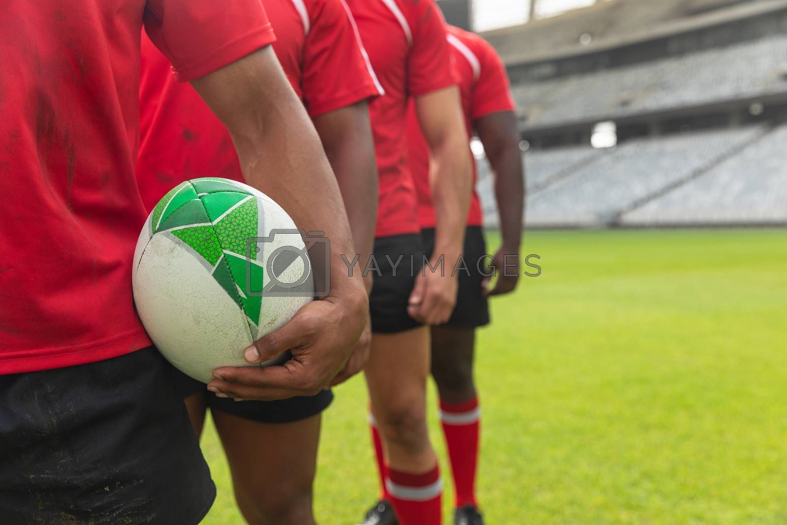 Mid section close up of diverse male rugby players standing together with rugby ball in stadium.