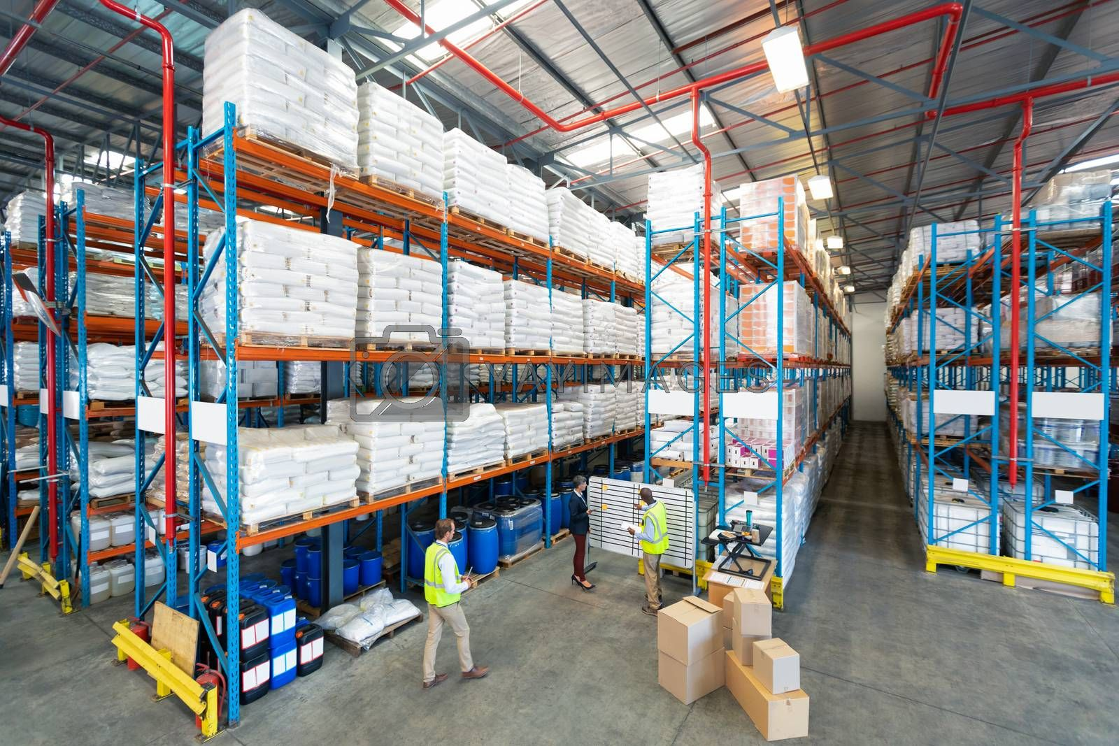 High angle view of mature diverse warehouse staff discussing over whiteboard in warehouse. This is a freight transportation and distribution warehouse. Industrial and industrial workers concept