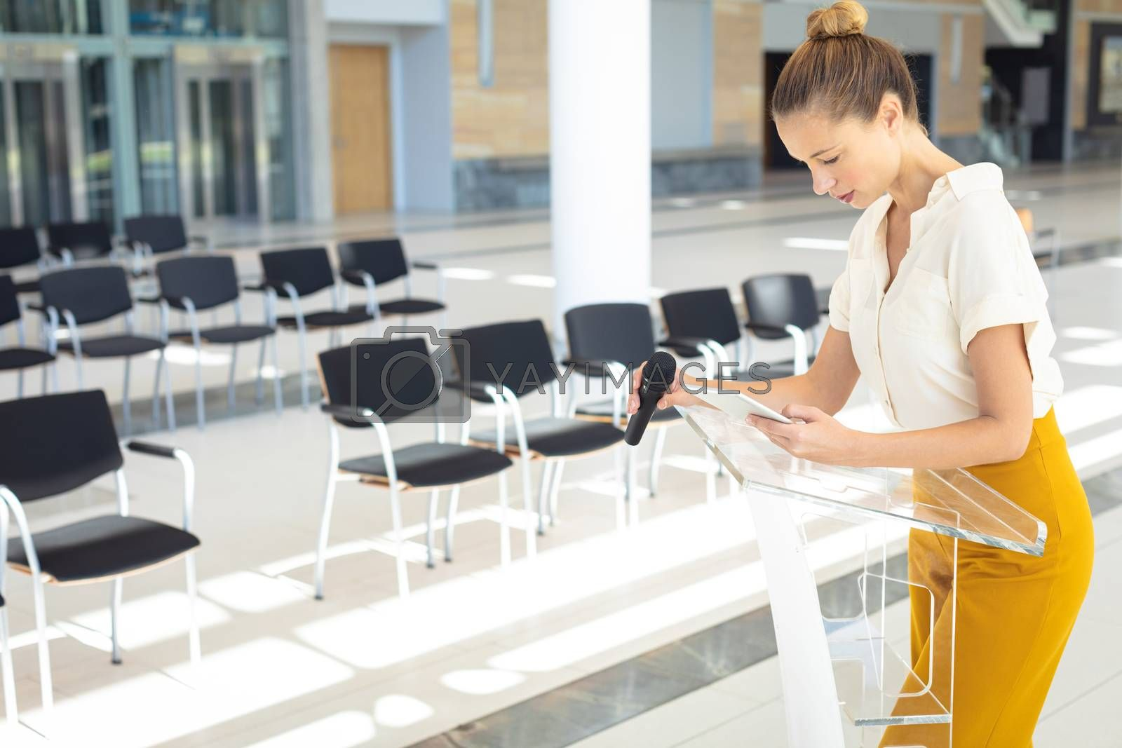 Side view of young Caucasian female executive standing with microphone while looking at digital tablet in empty conference room