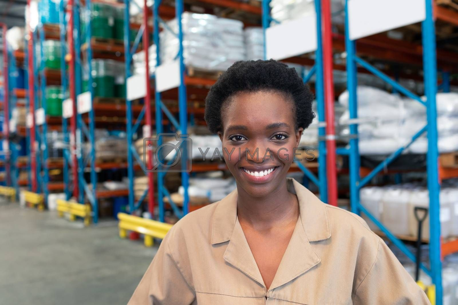 Portrait close-up of beautiful young African-american female staff looking at camera in warehouse. This is a freight transportation and distribution warehouse. Industrial and industrial workers concept