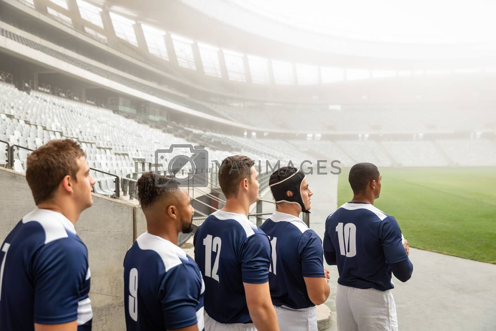Side View of group of male rugby players standing at the entrance of stadium in a row for match