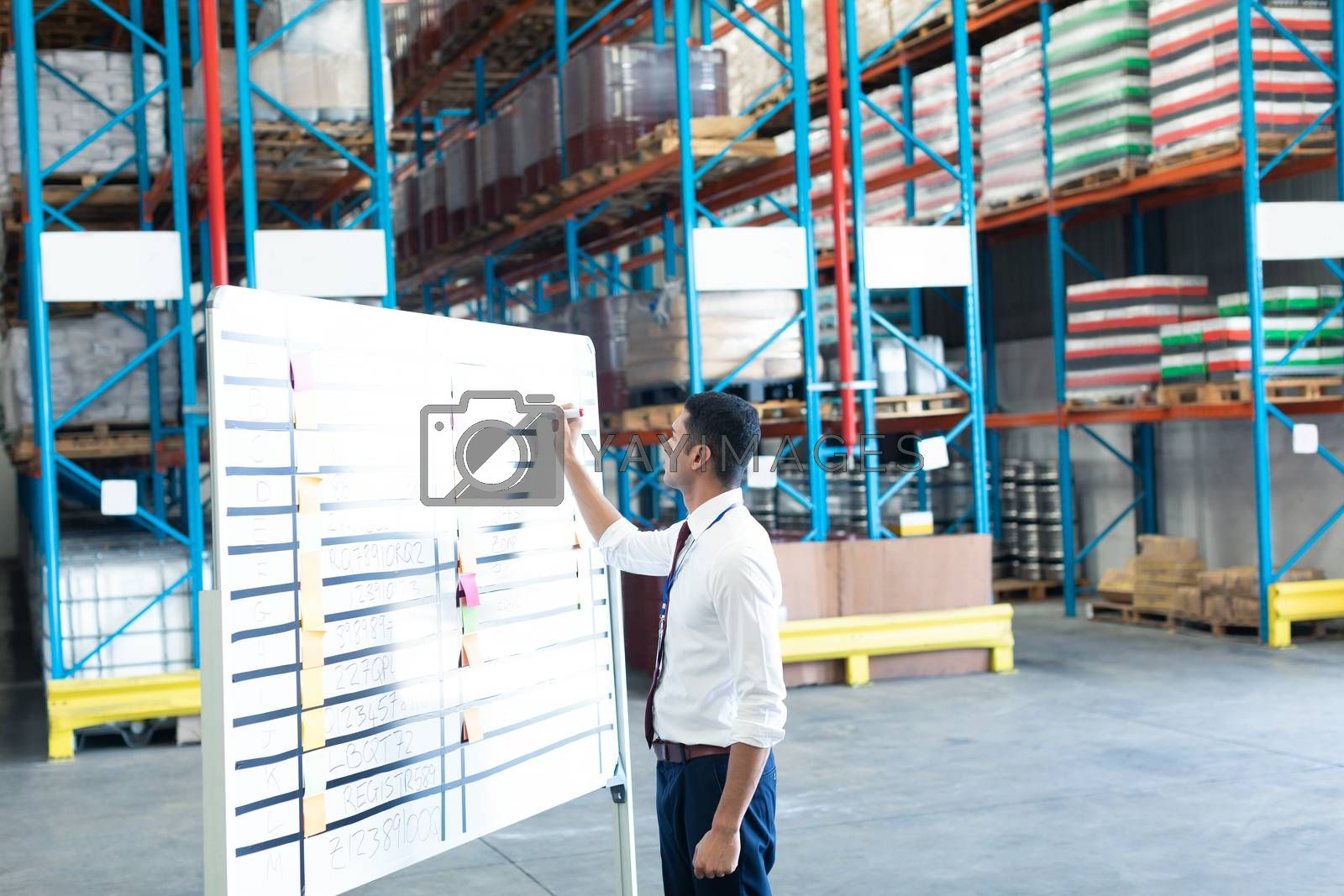 Side view of handsome young Caucasian male staff writing on sticky notes in warehouse. This is a freight transportation and distribution warehouse. Industrial and industrial workers concept