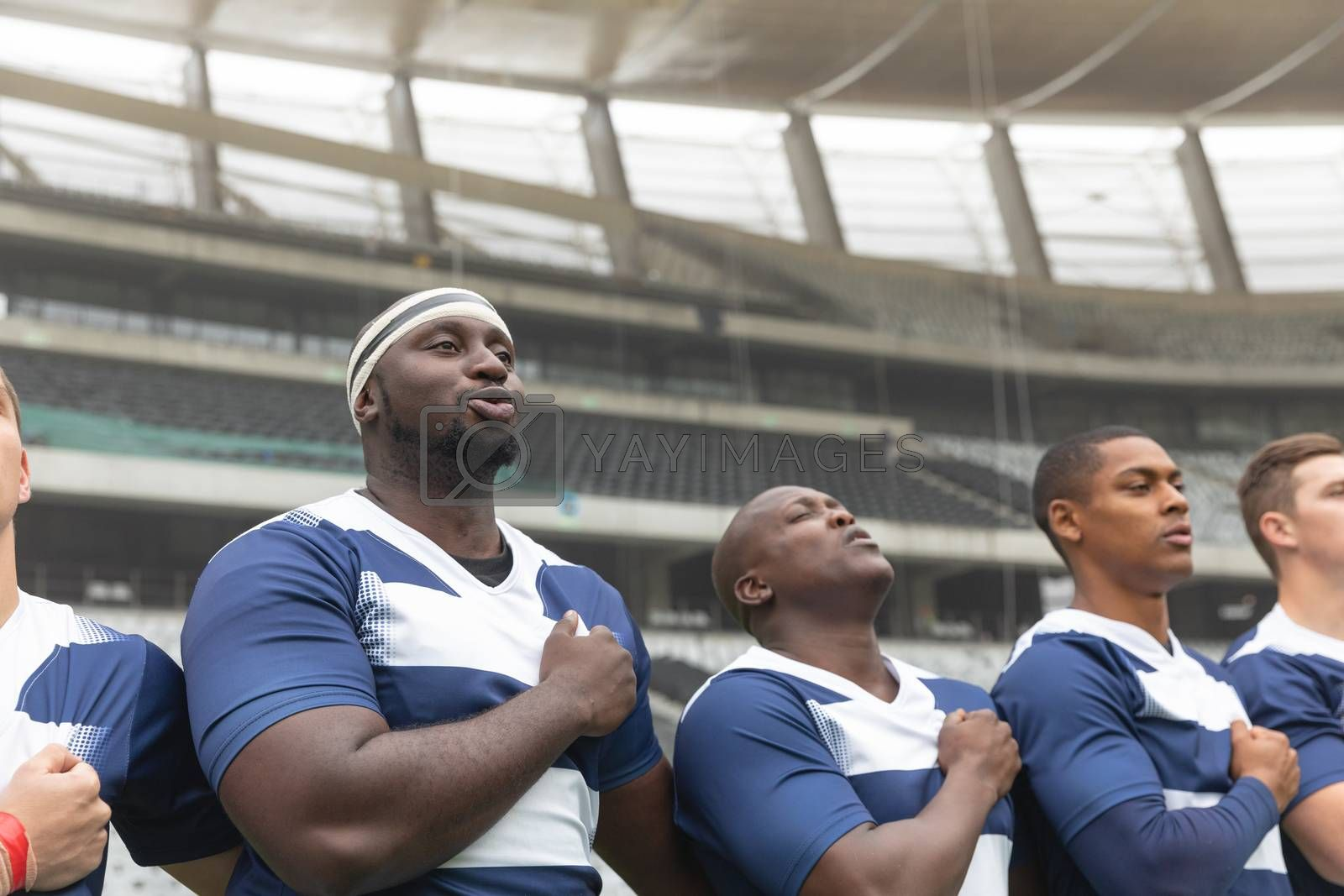 Side view of group of diverse male rugby players taking pledge together in stadium