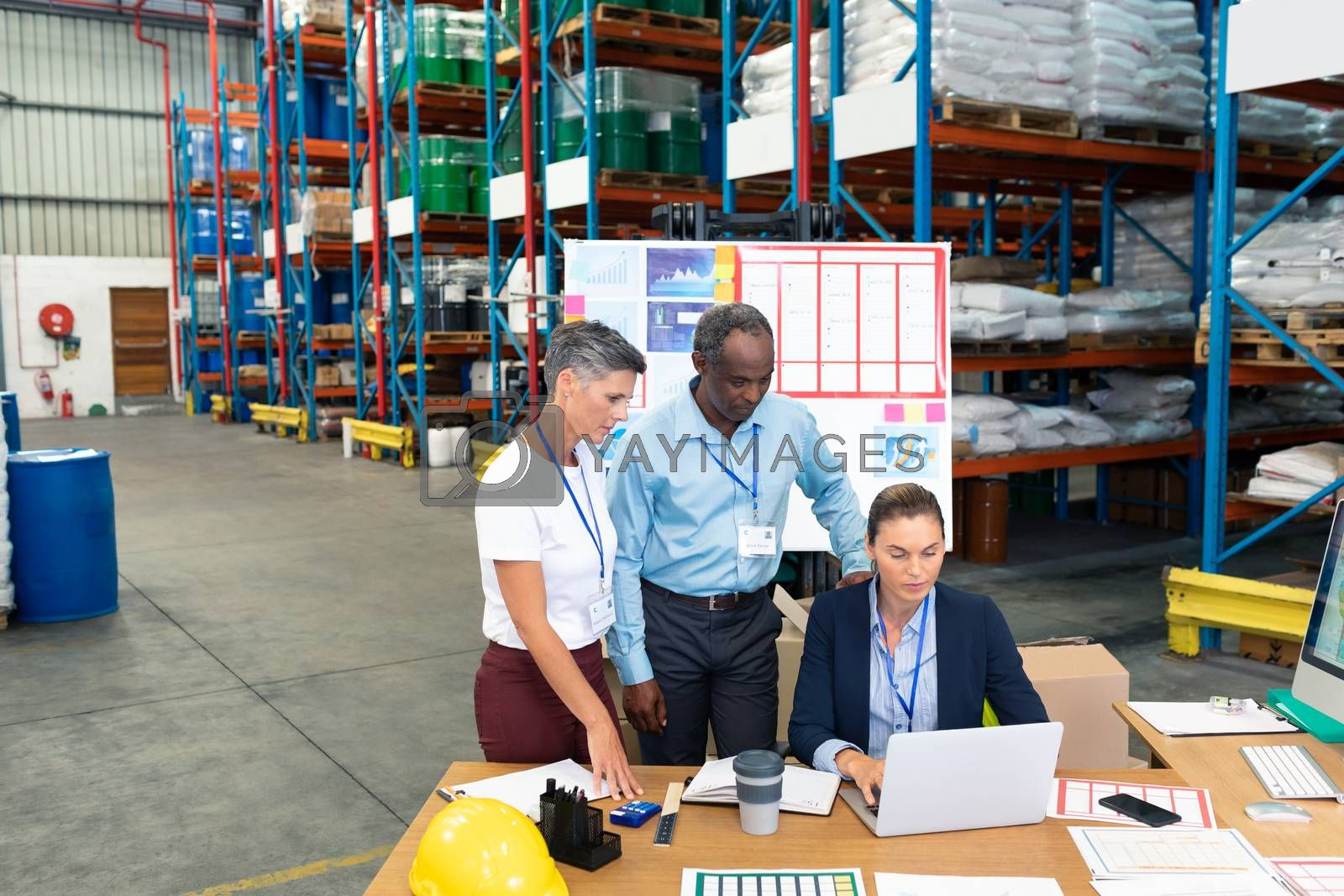 Front view of beautiful Caucasian female manager with her diverse coworkers discussing over laptop at desk in warehouse. This is a freight transportation and distribution warehouse. Industrial and industrial workers concept
