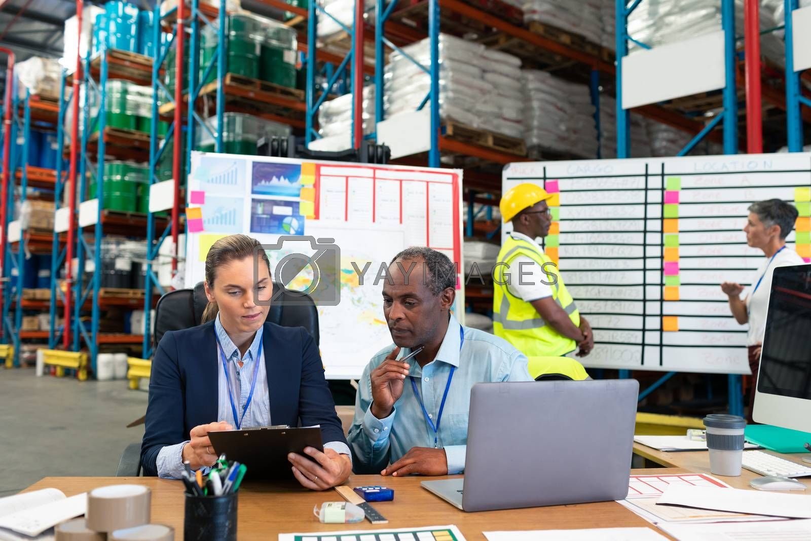 Front view of Caucasian female manager and African-american male supervisor discussing over clipboard at desk in warehouse. This is a freight transportation and distribution warehouse. Industrial and industrial workers concept