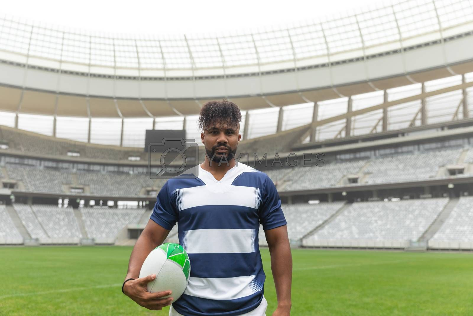 Portrait of African American rugby player standing with rugby ball in stadium