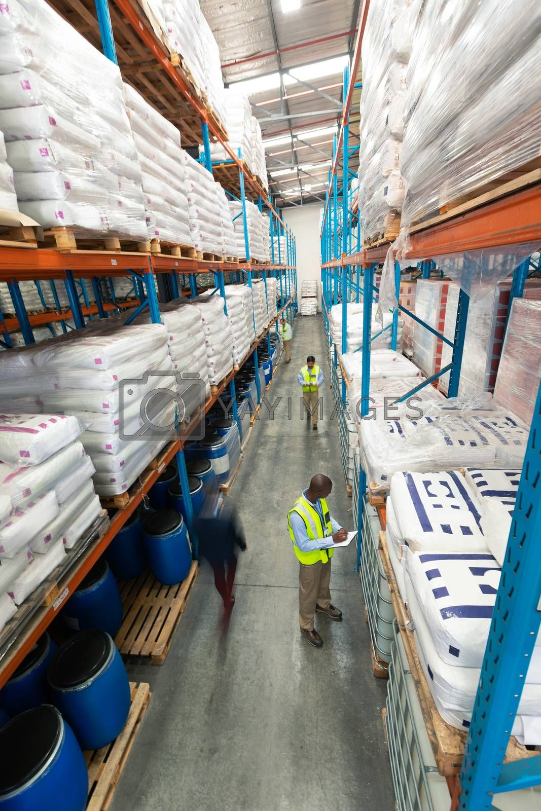 High angle view of diverse warehouse staff checking stocks in aisle in warehouse. They are holding clipboards and writing in it. This is a freight transportation and distribution warehouse. Industrial and industrial workers concept