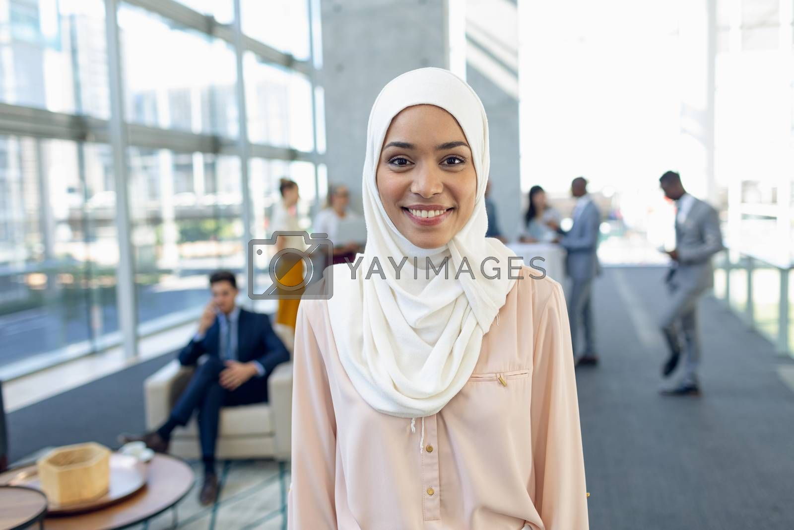 Front view of young pretty businesswoman in hijab looking at camera while standing in modern office. Behind her, colleagues interacting with each other.
