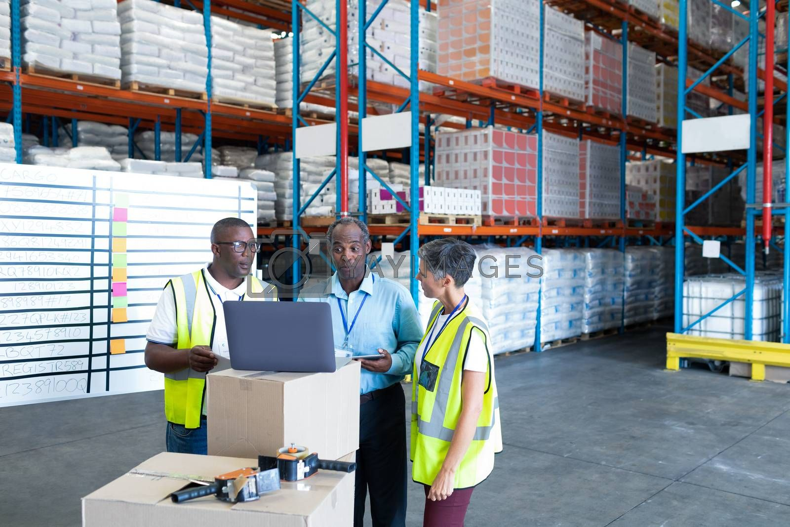 Front view of mature diverse warehouse staffs discussing over laptop in warehouse. This is a freight transportation and distribution warehouse. Industrial and industrial workers concept