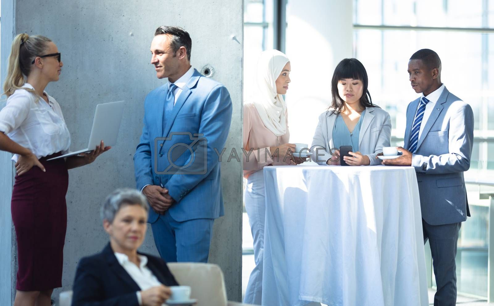 Front view of groups of diverse colleagues interacting with each other in modern office.
