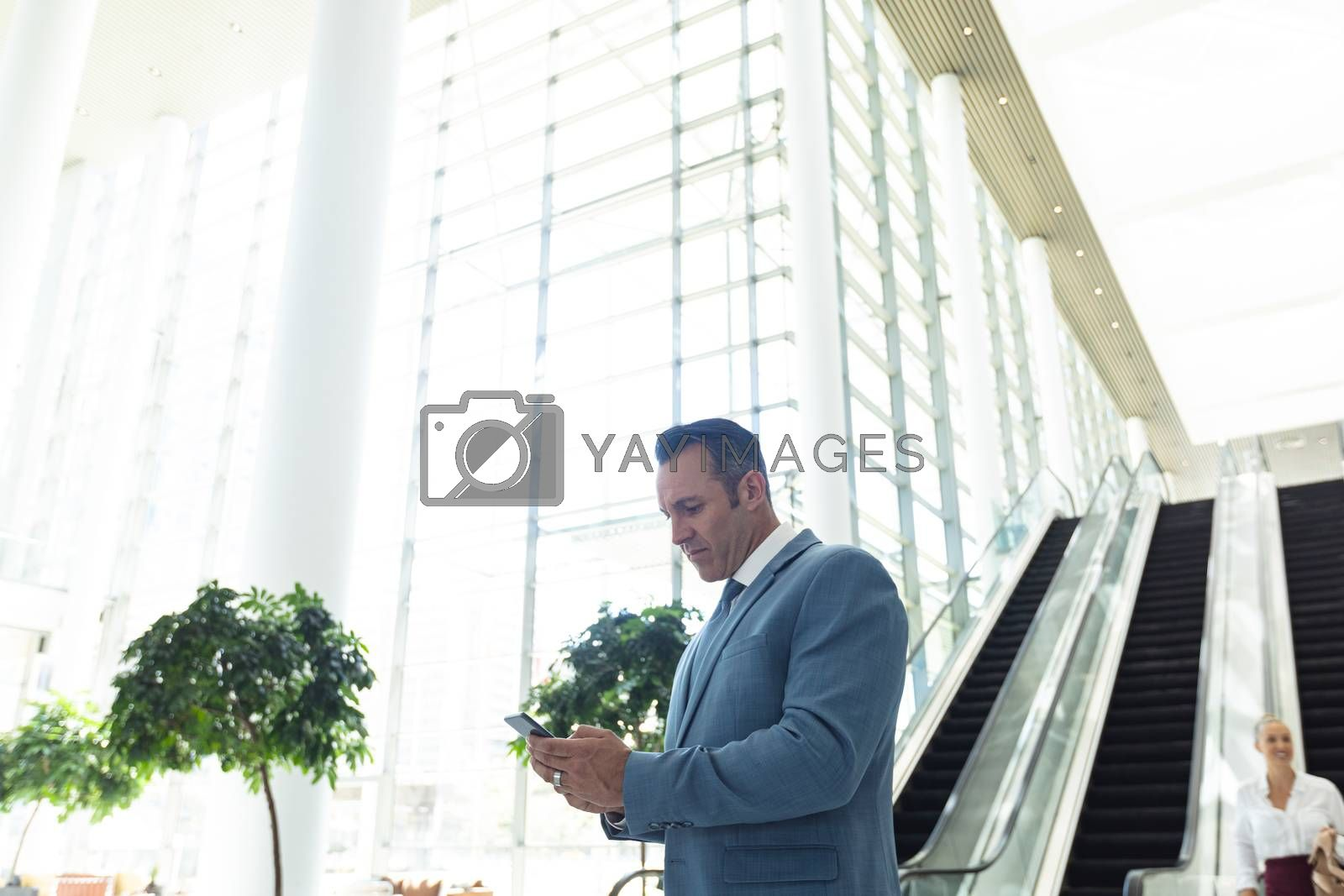 Side view of mature Caucasian businessman looking at mobile phone while standing in modern office