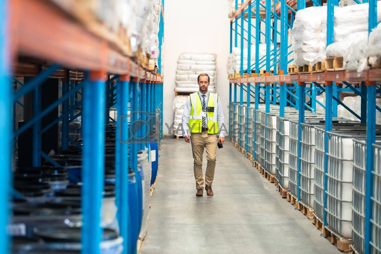 Front view of Caucasian male supervisor walking in aisle of warehouse. This is a freight transportation and distribution warehouse. Industrial and industrial workers concept
