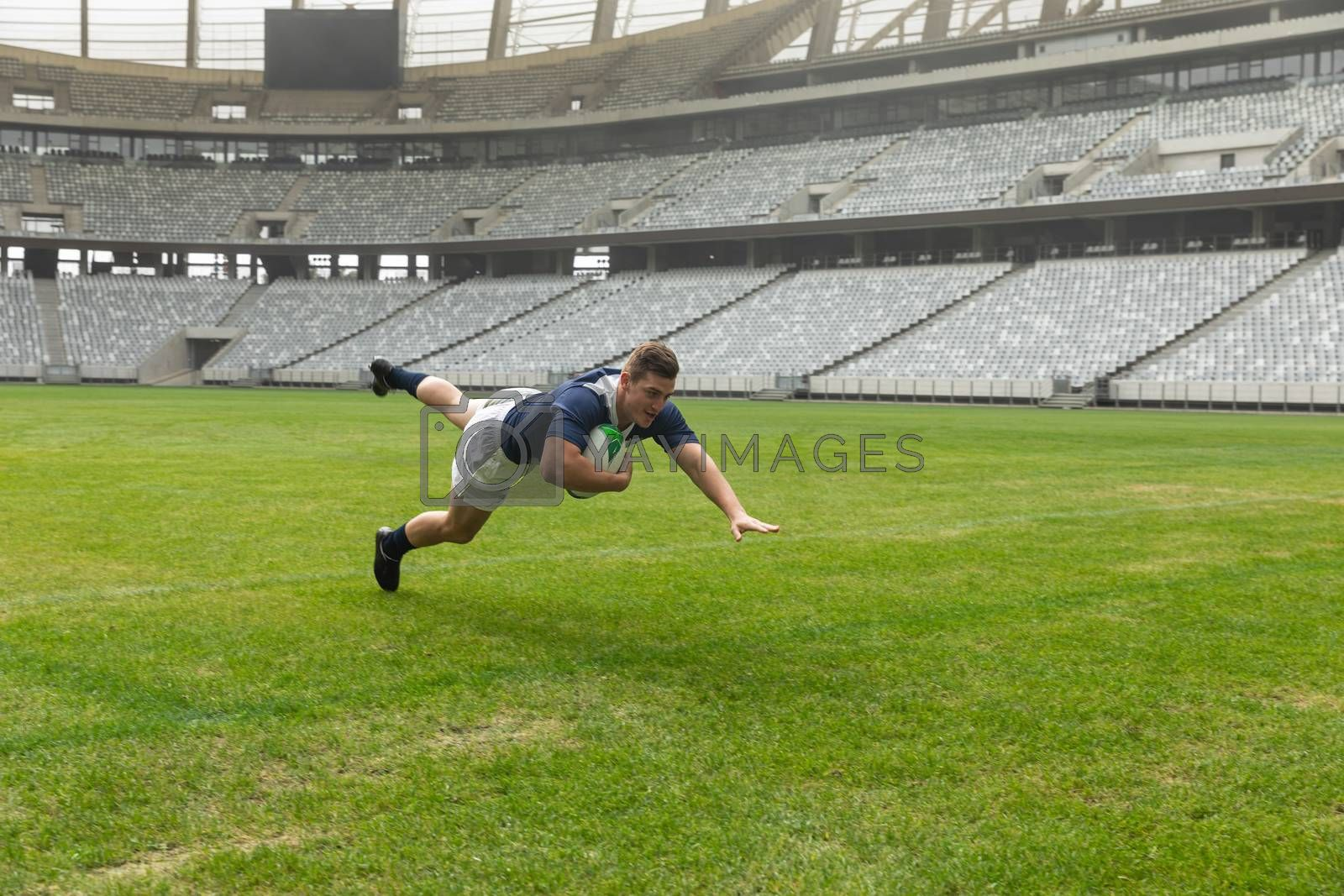 Side view of young Caucasian male rugby player playing rugby in stadium