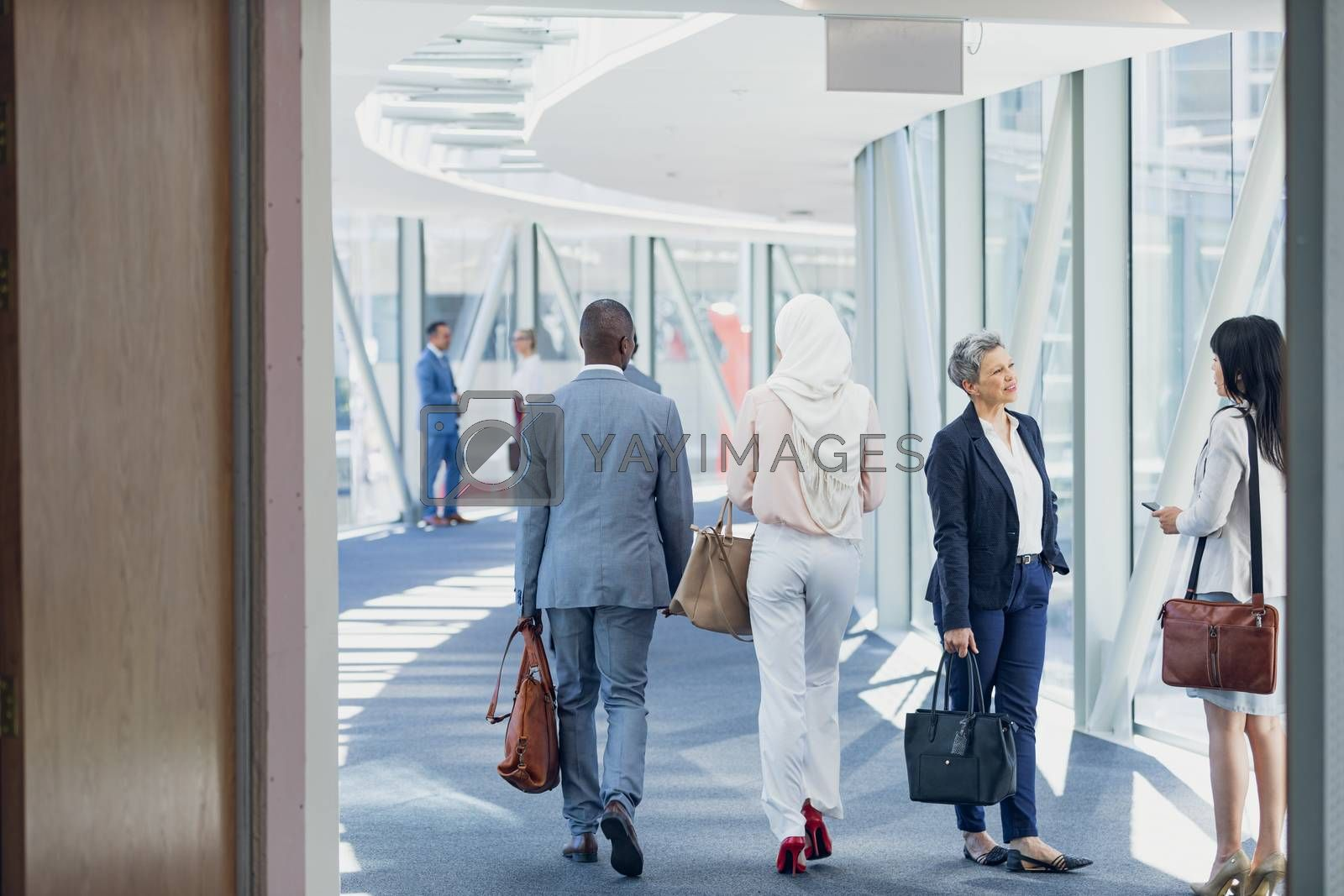 Rear view of business people walking in corridor in modern office