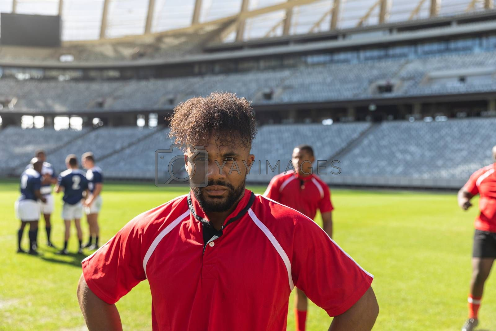 Portrait close up of active African American male rugby player standing in stadium. Diverse rugby team talking to each other in the background.