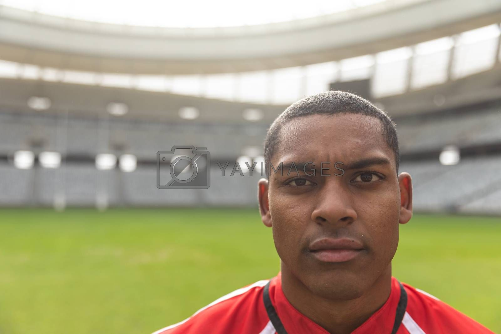 Portrait close up of handsome African American rugby player looking at camera in the stadium.