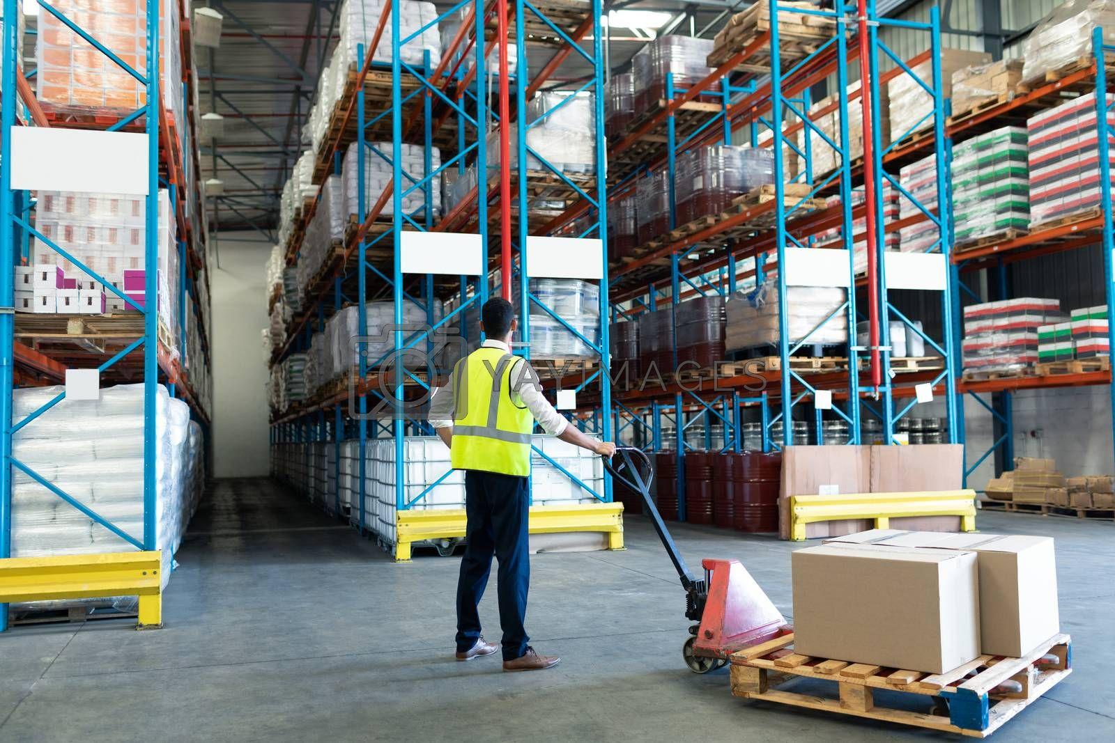 Rear view of Caucasian male staff using pallet jack in warehouse. This is a freight transportation and distribution warehouse. Industrial and industrial workers concept