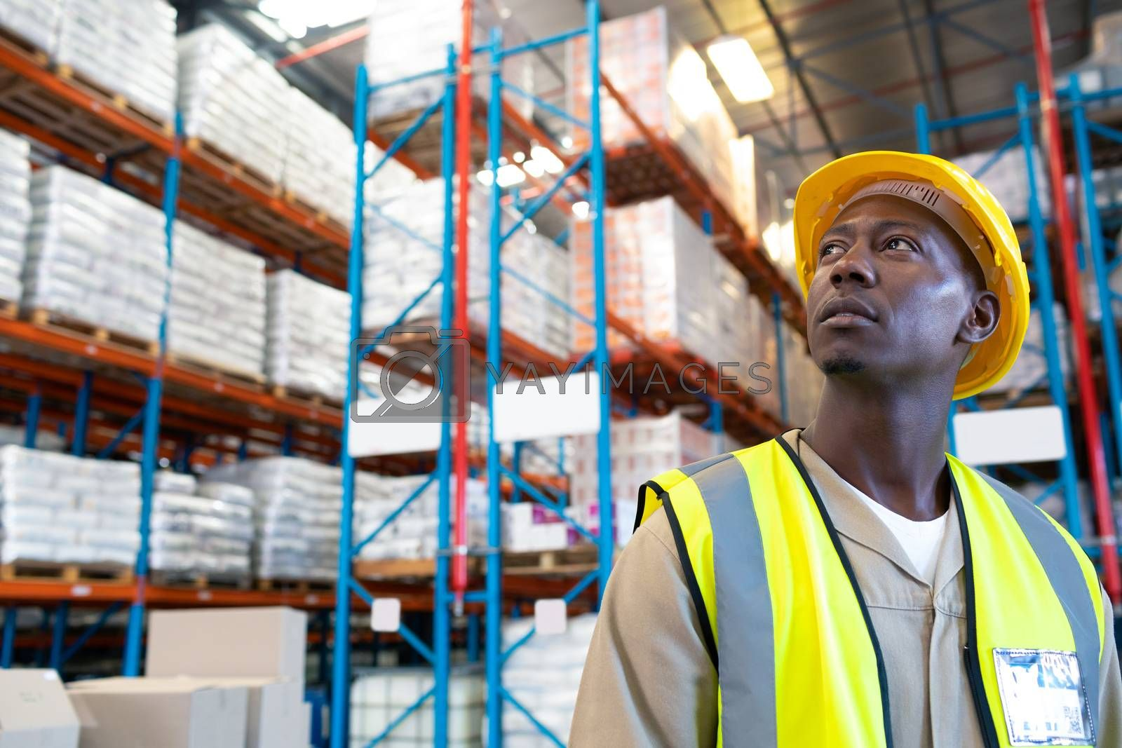 Close-up of thoughtful African-american male worker looking away in warehouse. This is a freight transportation and distribution warehouse. Industrial and industrial workers concept