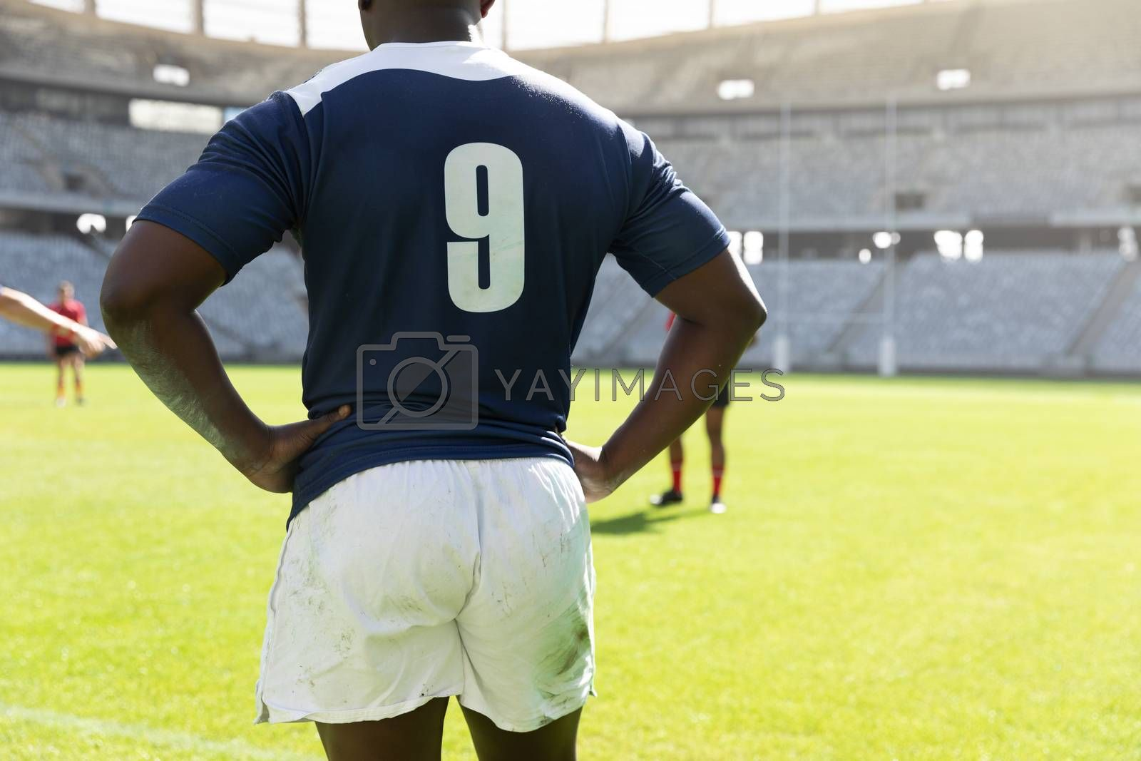 Mid section of handsome african american male rugby player standing with hands on hip in the stadium on a sunny day.