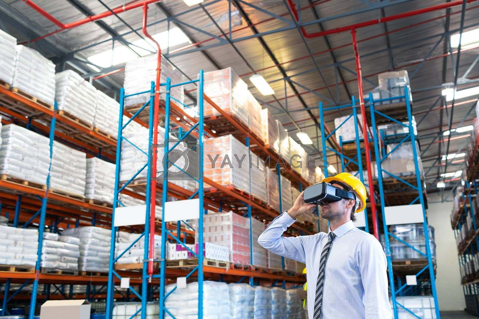 Front view of handsome Caucasian male supervisor using virtual reality headset in warehouse. This is a freight transportation and distribution warehouse. Industrial and industrial workers concept