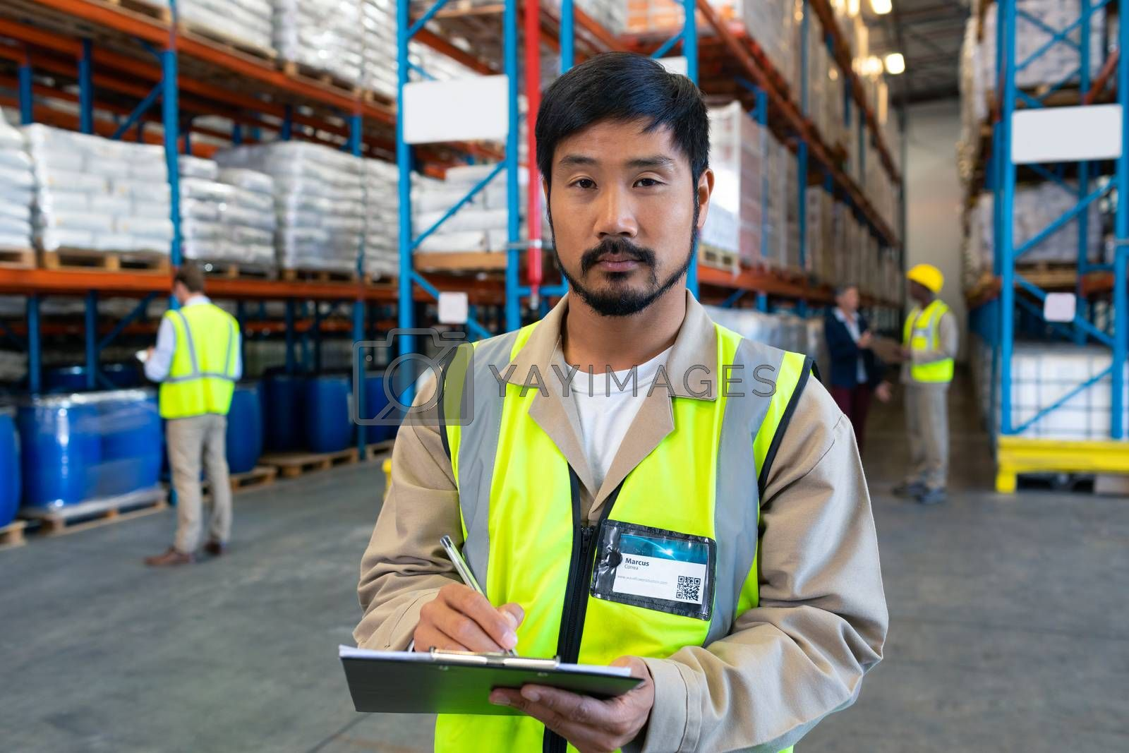Close-up of handsome Asian male worker looking at camera while writing on clipboard in warehouse. This is a freight transportation and distribution warehouse. Industrial and industrial workers concept