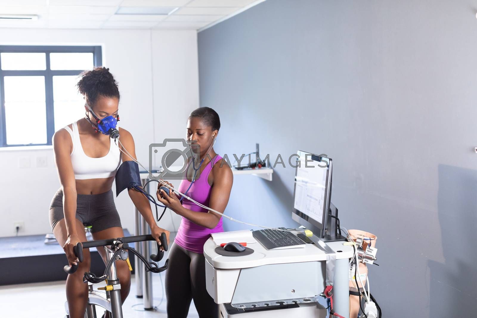 Front view of an African-American athletic woman doing a fitness test using a mask connected to a monitor while riding an exercise bike and an African-American woman measuring her blood pressure inside a room at a sports center. Bright modern gym with fit healthy people working out and training. Athlete testing themselves with cardiovascular fitness test on exercise bike
