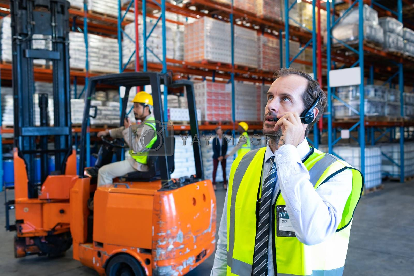 Front view of handsome Caucasian male supervisor talking on headset in warehouse. Diverse colleagues working in the background. This is a freight transportation and distribution warehouse. Industrial and industrial workers concept