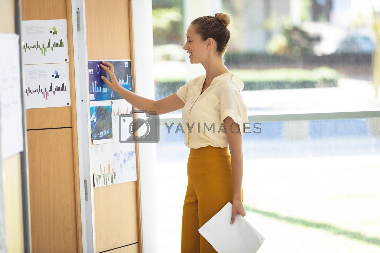 Side view of young Caucasian female executive looking at graphics while standing in modern office