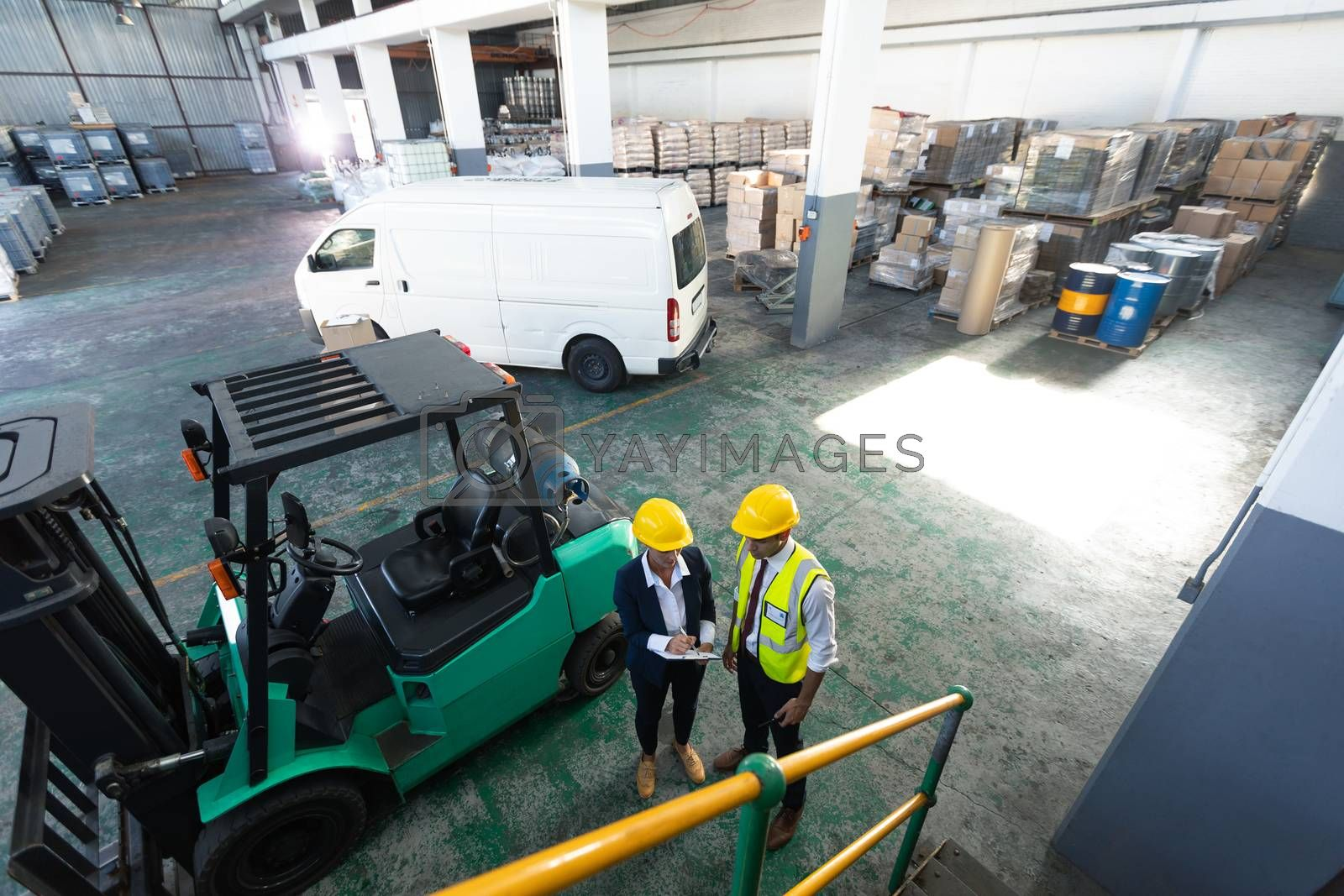 High angle view of Caucasian female manager and male supervisor discussing over clipboard in warehouse. This is a freight transportation and distribution warehouse. Industrial and industrial workers concept