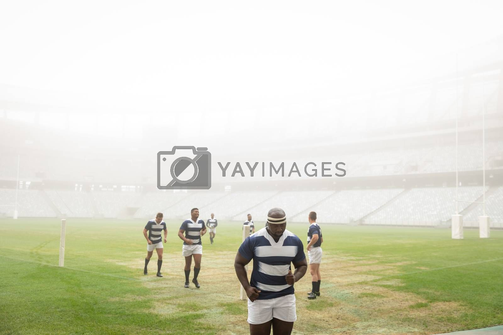 Front view of Group of diverse male rugby players running in stadium