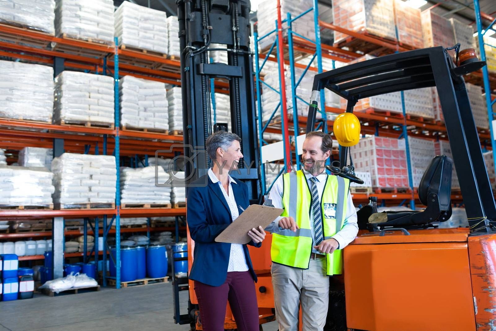Front view of happy mature Caucasian male and female staff interacting with each other near forklift in warehouse. This is a freight transportation and distribution warehouse. Industrial and industrial workers concept