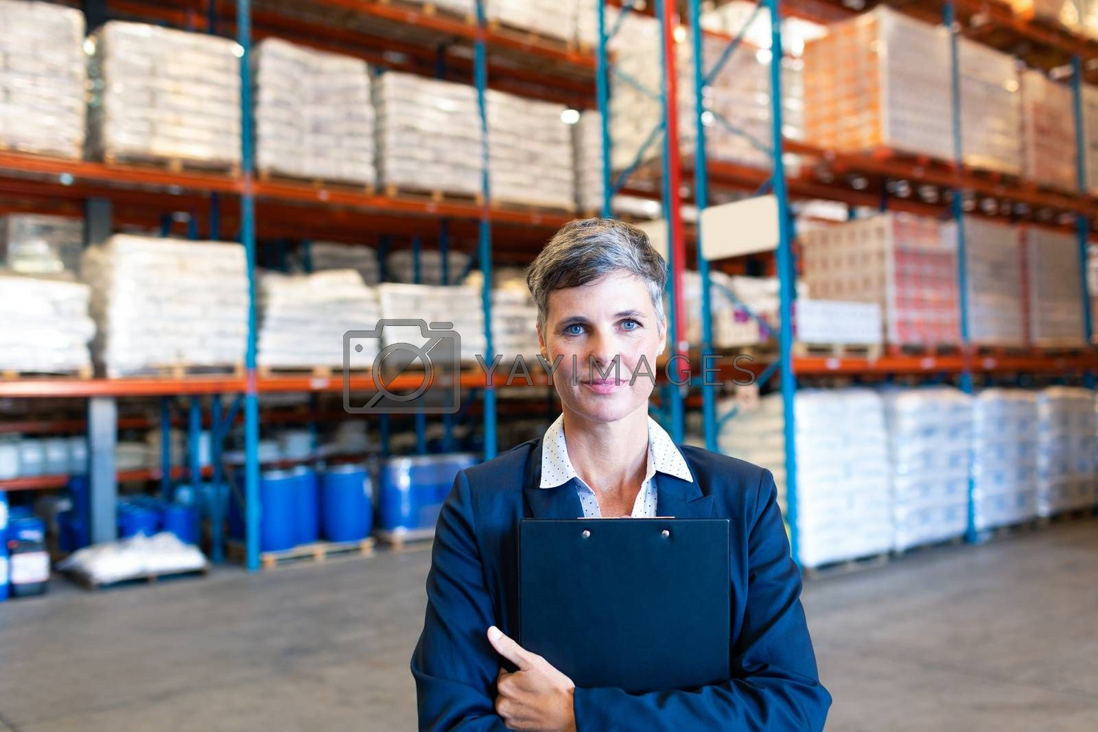Portrait of beautiful mature Caucasian female manager holding clipboard and looking at camera in warehouse. This is a freight transportation and distribution warehouse. Industrial and industrial workers concept