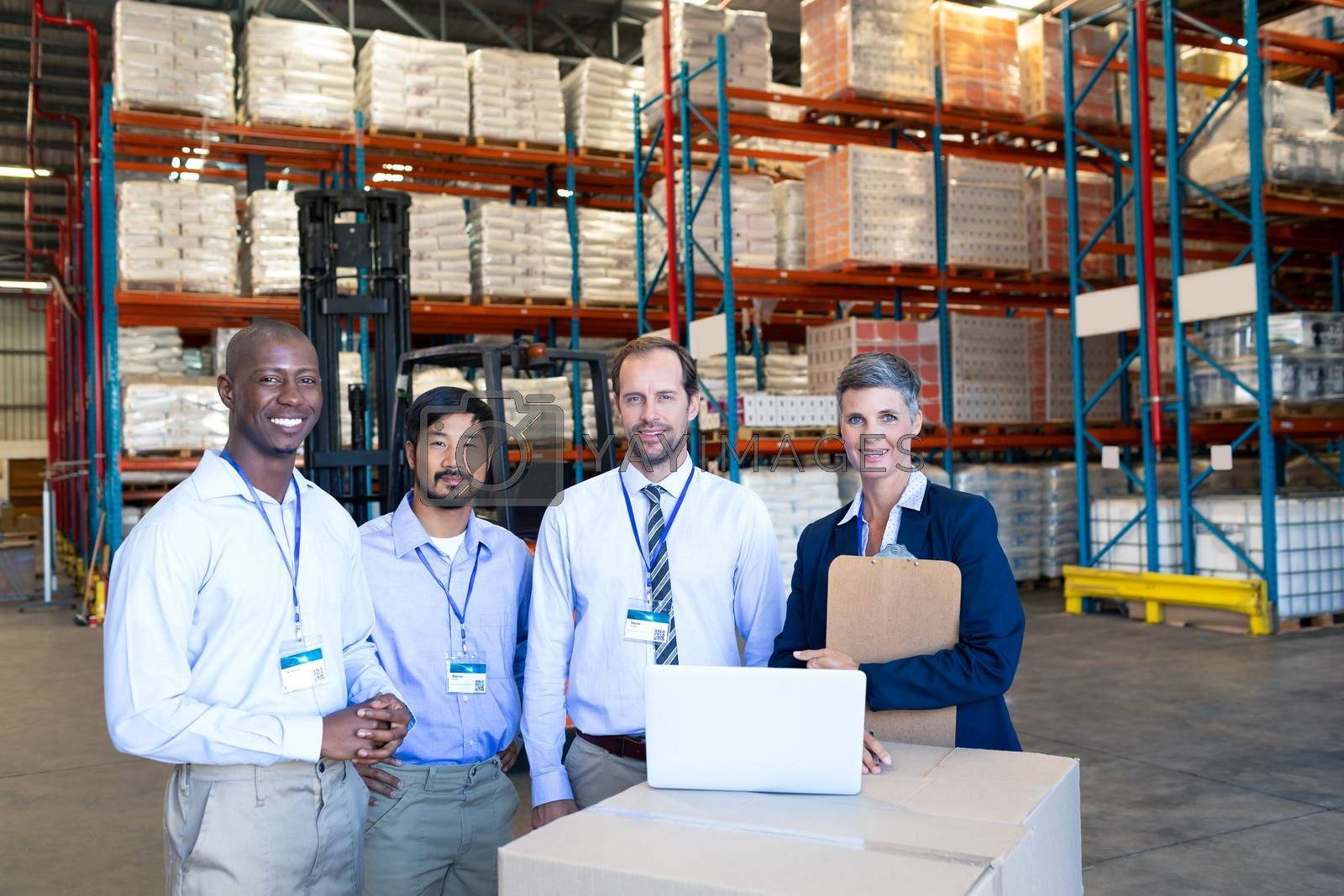 Front view of happy mature Caucasian staff looking at camera in warehouse. This is a freight transportation and distribution warehouse. Industrial and industrial workers concept
