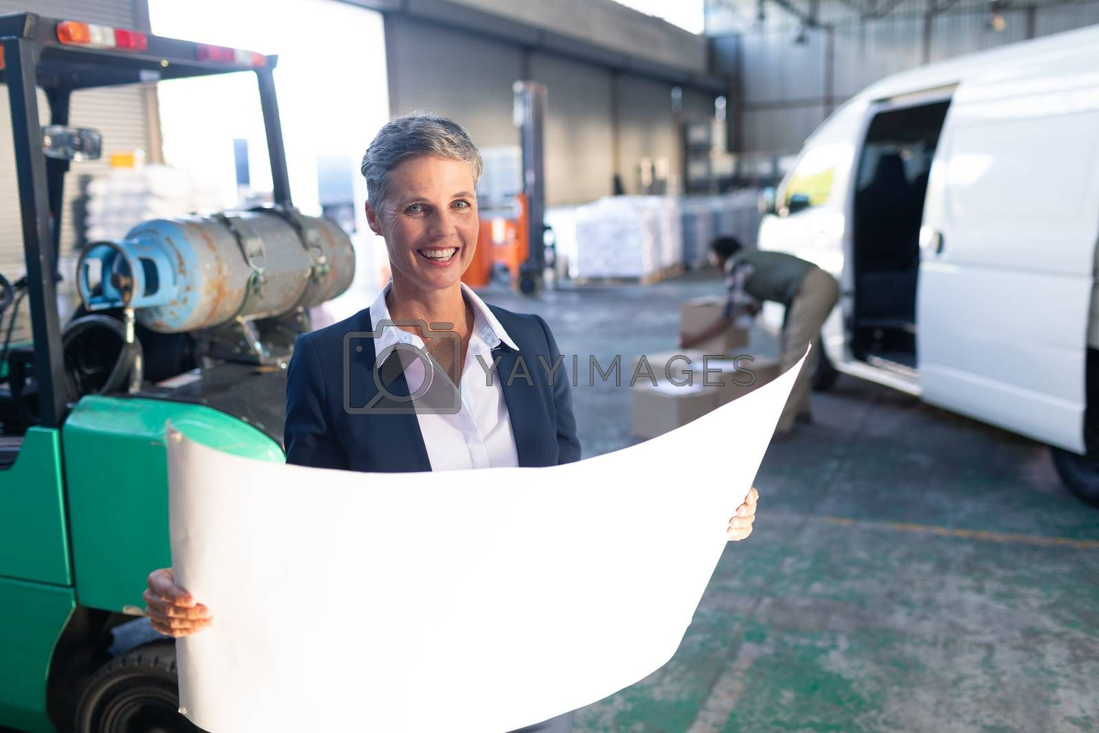 Portrait of happy Caucasian female manager looking at blueprint in warehouse. This is a freight transportation and distribution warehouse. Industrial and industrial workers concept