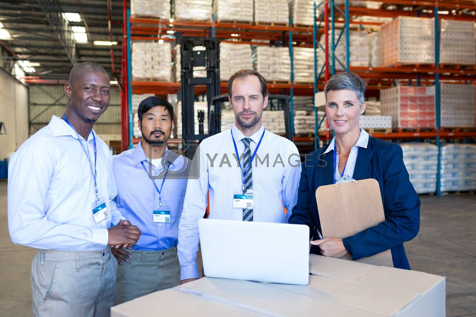 Front view of mature diverse staff looking at camera in warehouse. This is a freight transportation and distribution warehouse. Industrial and industrial workers concept
