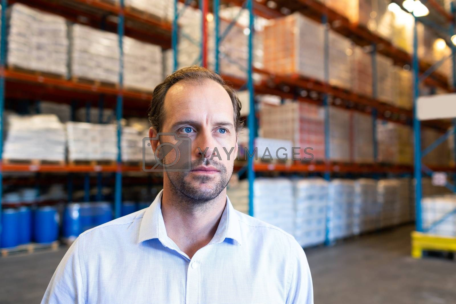 Portrait close-up of handsome mature Caucasian male supervisor looking away in warehouse. This is a freight transportation and distribution warehouse. Industrial and industrial workers concept