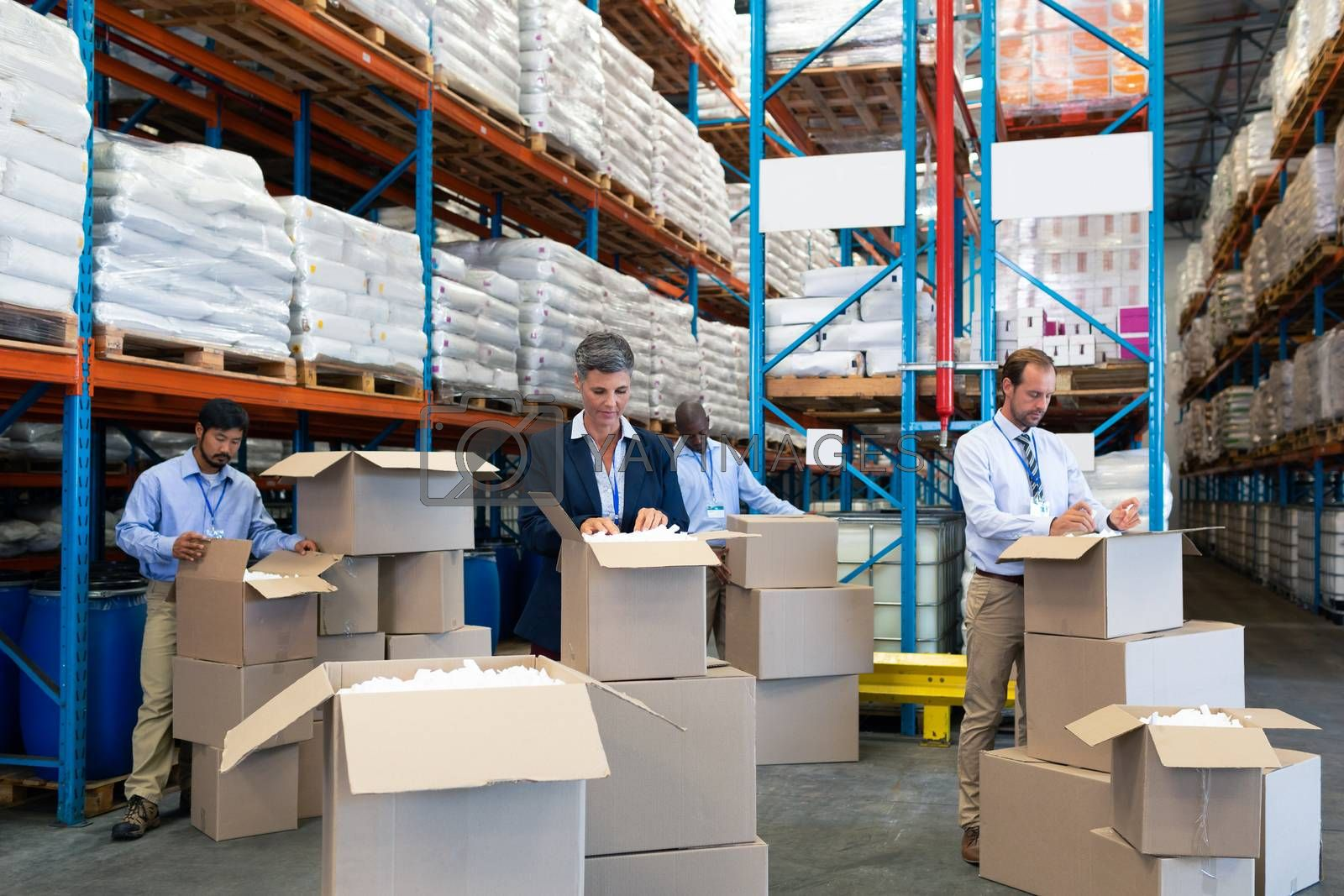 Front view of diverse mature staff checking stocks in warehouse. They are standing in front of cardboard boxes. This is a freight transportation and distribution warehouse. Industrial and industrial workers concept