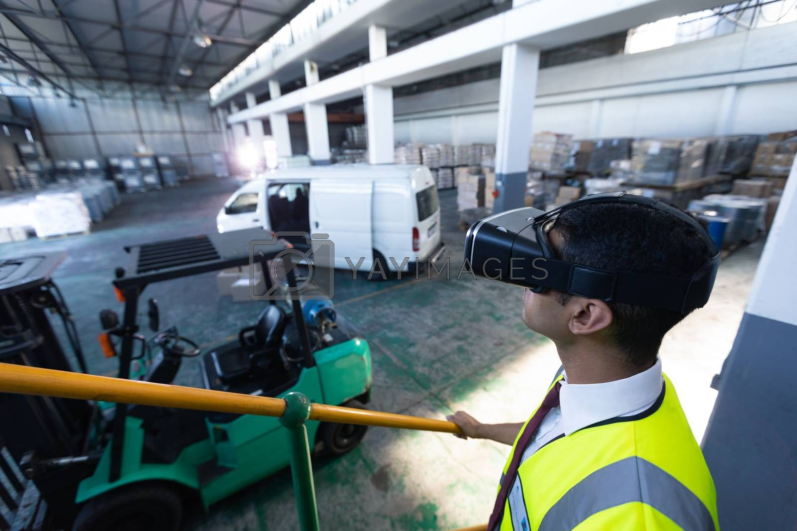 Close-up of Caucasian male supervisor using virtual reality headset in warehouse. This is a freight transportation and distribution warehouse. Industrial and industrial workers concept