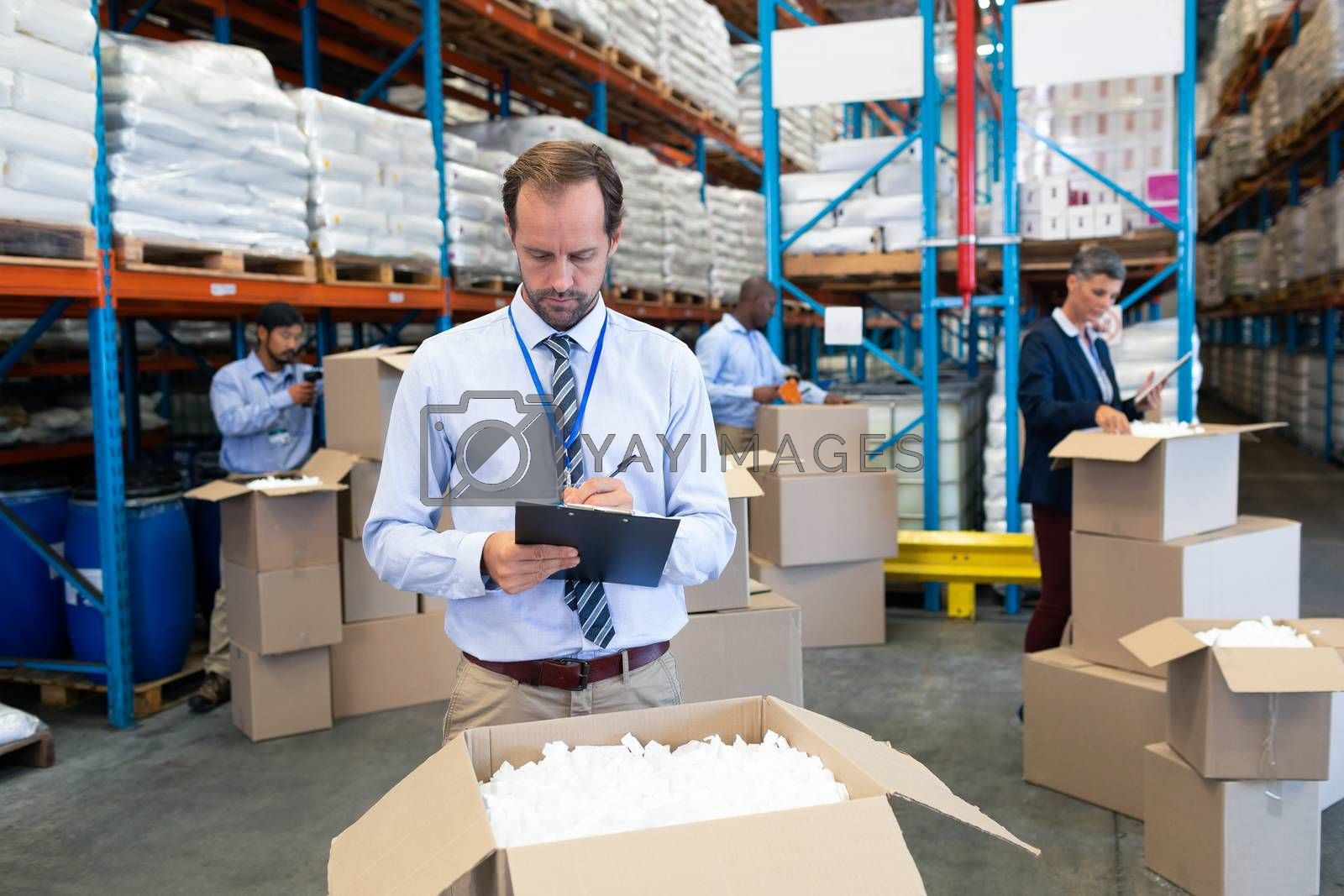 Front view of handsome mature Caucasian male supervisor writing on clipboard in warehouse. Diverse workers checking stock in cardboard boxes behind supervisor. This is a freight transportation and distribution warehouse. Industrial and industrial workers concept