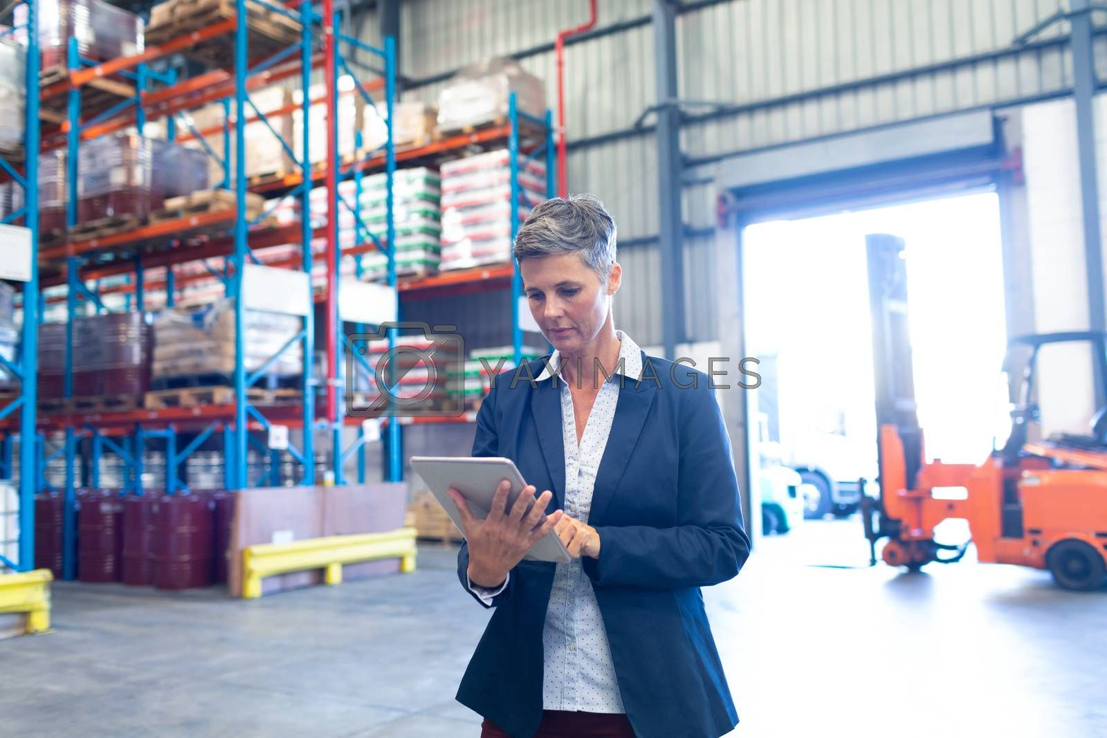 Front view of pretty mature Caucasian female manager using digital tablet in warehouse. This is a freight transportation and distribution warehouse. Industrial and industrial workers concept