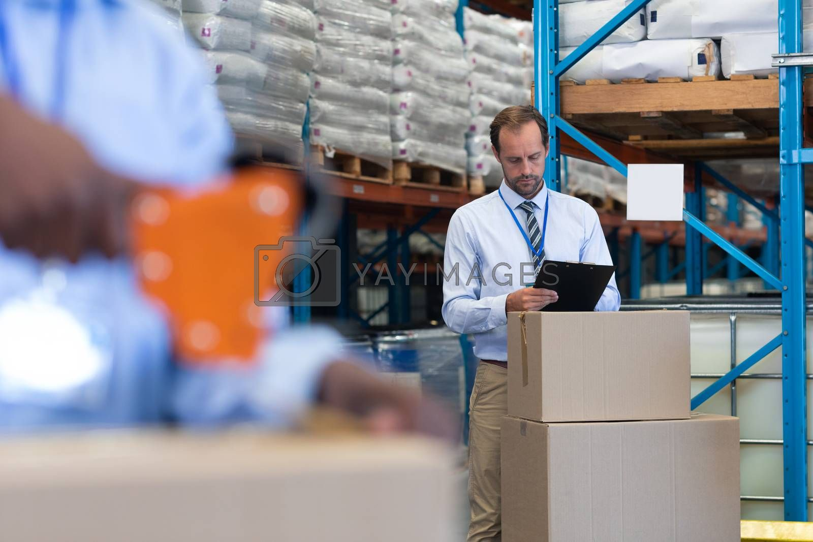 Front view of handsome mature Caucasian male supervisor working on clipboard while African-american staff works on the foreground in warehouse. This is a freight transportation and distribution warehouse. Industrial and industrial workers concept