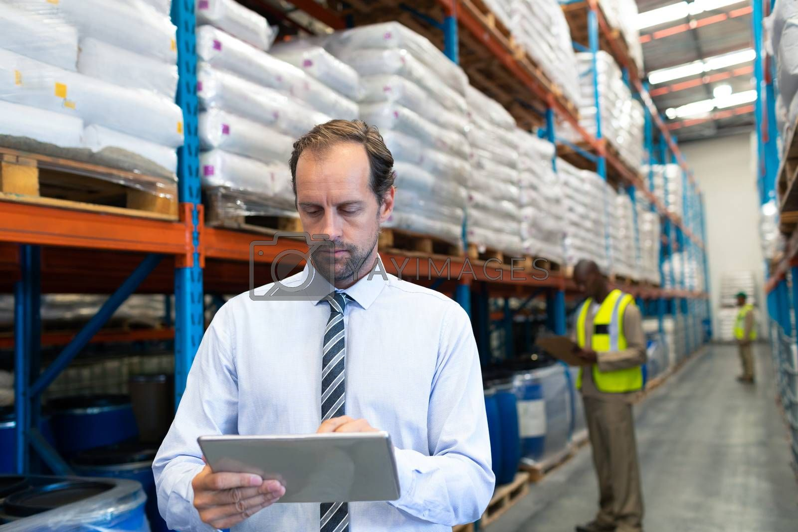 Front view of mature Caucasian male supervisor working on digital tablet in warehouse. This is a freight transportation and distribution warehouse. Industrial and industrial workers concept