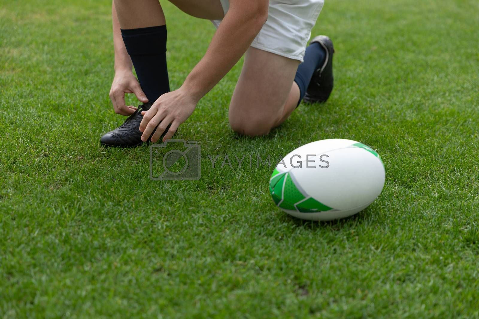 Low section of Caucasian male rugby player tying shoelaces in the stadium