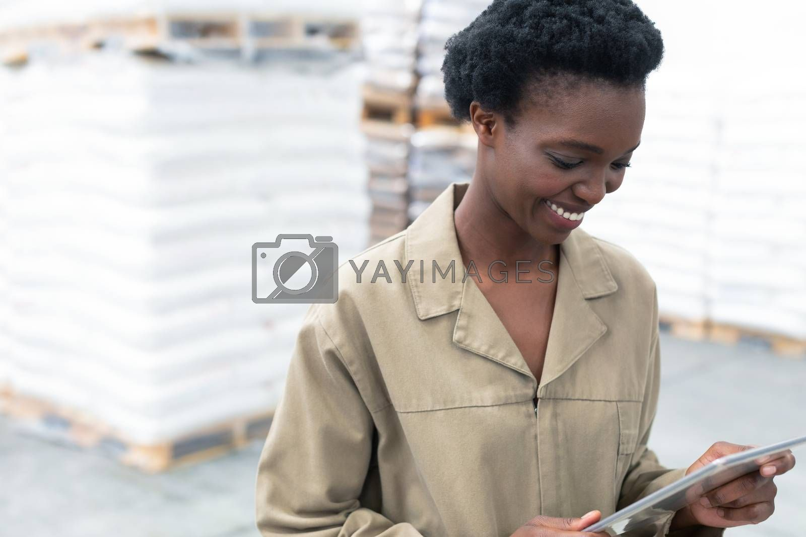 Close-up of beautiful young African-american female worker working on digital tablet in warehouse. This is a freight transportation and distribution warehouse. Industrial and industrial workers concept