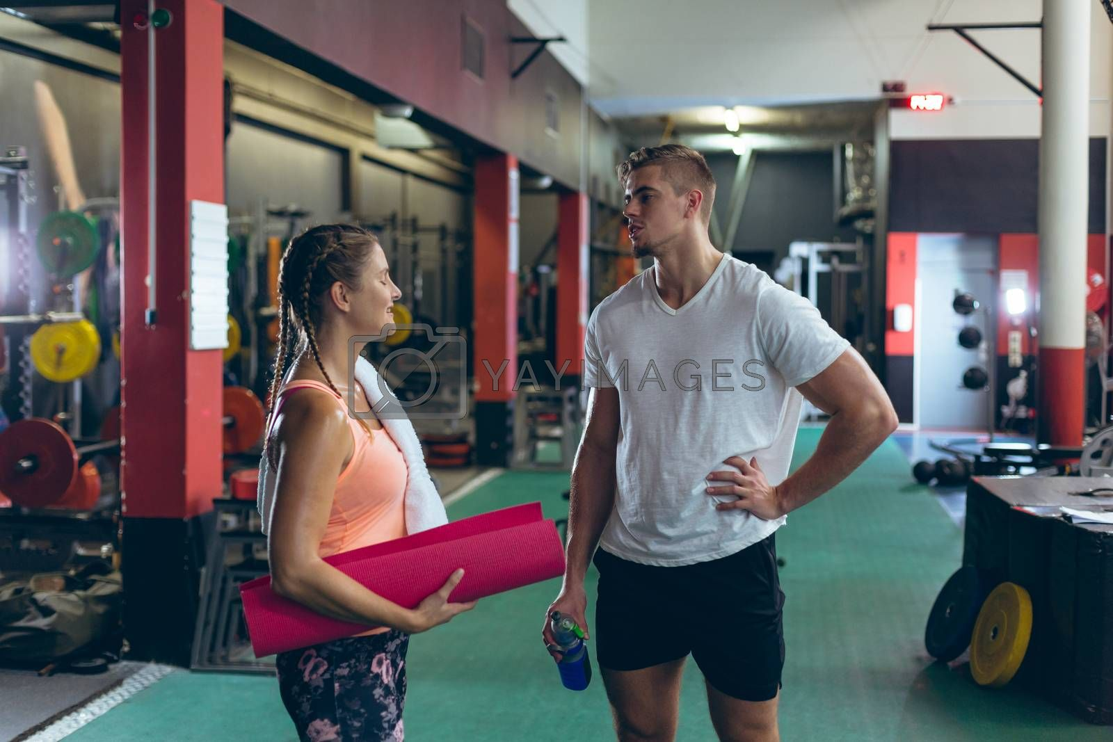 Front view of young Caucasian male and female athlete talking with each other in fitness studio. Bright modern gym with fit healthy people working out and training